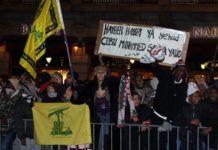 Da Israel-venner afholder en støtte demonstration for Israel i Oslo den 8. januar 2009, holder nogle mod-demonstranter deres banner op. Teksten viser sig at være en trussel om at gentage Muhammads massakre på de tre jødiske storfamilier i Khaibar. Læg også mærke til de gule flag fra terrororganisationen Hizbollah (arkivfoto: Odd Østtveit)