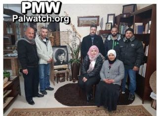 """Ungdomslejren """"Brothers of Dalal"""" - under PLO. - viser stolt ledelsen ved siden af et fotografi af Dalal Mughrabi"""